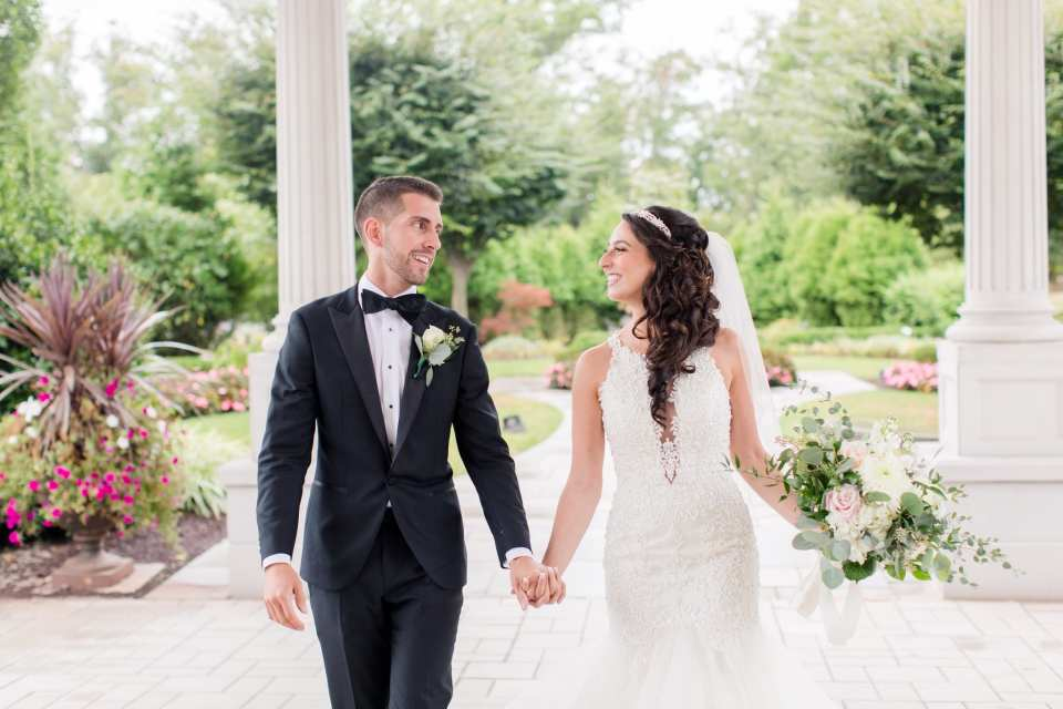 Bride and groom holding hands, looking at one another while walking towards the camera