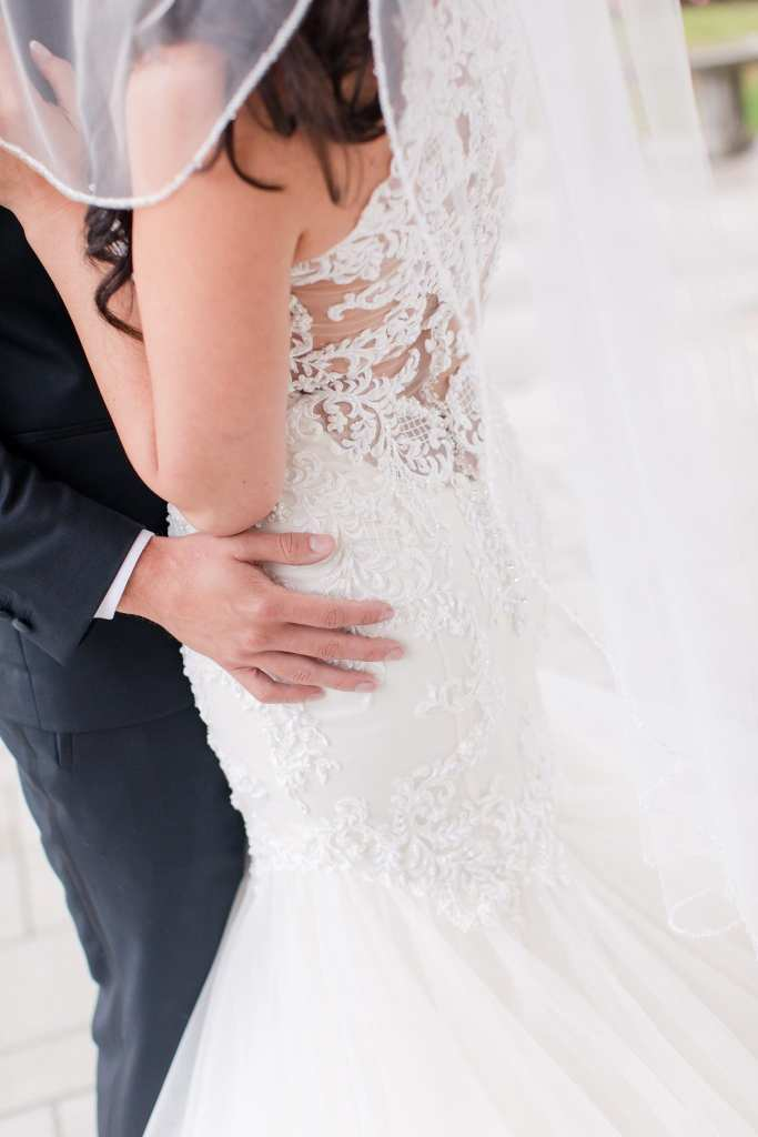 Photo of the back of the brides Maggie Sottero gown, as she is held at the waist by her groom