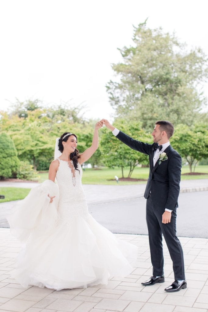 The groom in a tuxedo by Enzo twirls his bride in her Maggie Sottero Gown, the palace at somerset park wedding photos