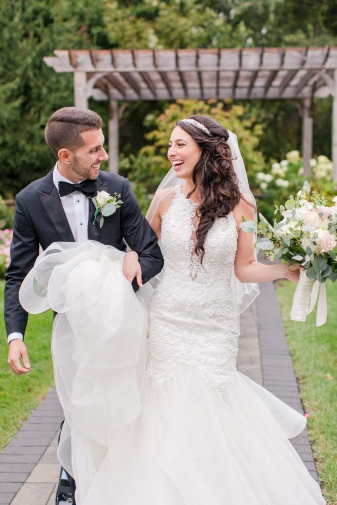 The bride and groom laughing, looking at each other, arms linked, the brides train in both of their arms, her bouquet in her other hand by Jacquelines Florist