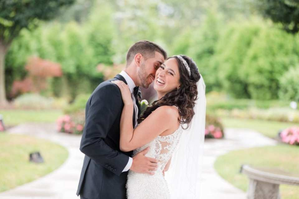 The bride laughing as her groom nuzzles her neck outdoors at the Palace at Somerset Park