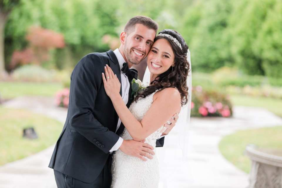 The bride and groom, he is slightly dipping her, her left hand is on his chest showing off her engagement ring. Her hair is by Celeste Moderno, makeup by Make Me Up Eva
