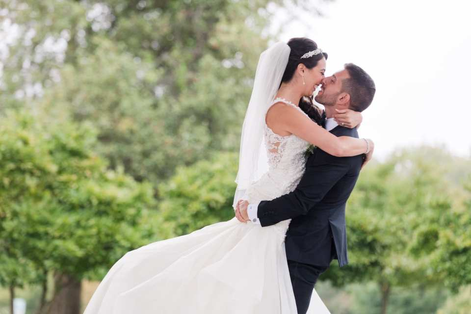 The groom lifting up his bride in the air, her arms wrapped around his neck, their noses touching