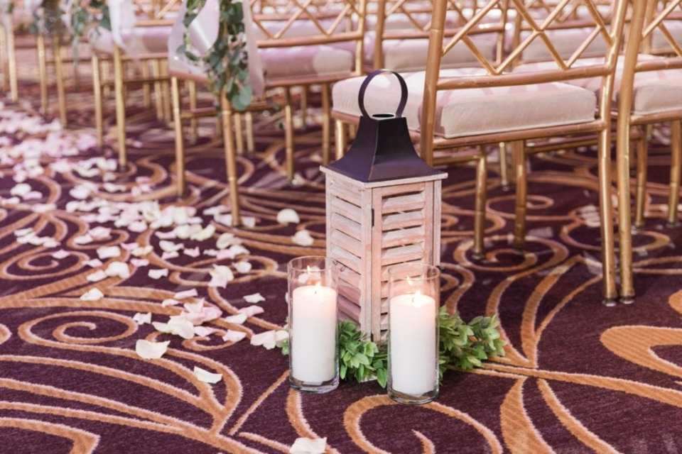 Wedding detail photo of aisle decor of candles, lanterns and rose petals by Jacquelines Florist