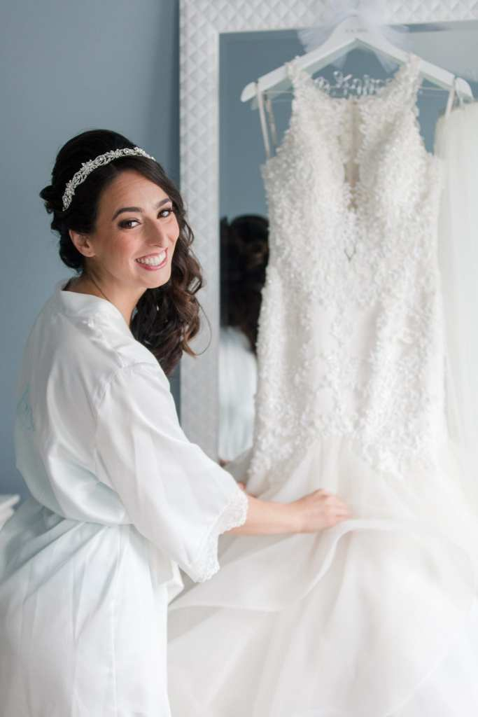 Bride in white robe examing her hanging Maggie Sottero gown while looking back at camera, smiling