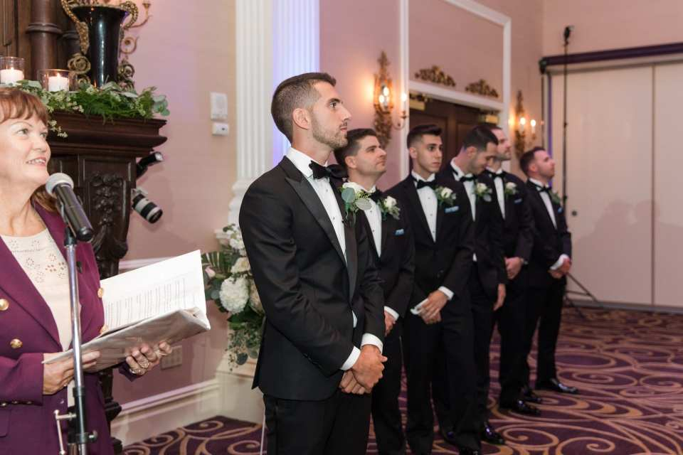 The groom waiting for his bride at the end of the aisle along with his groomsmen in their suits by Enzo at the Palace at Somerset Park