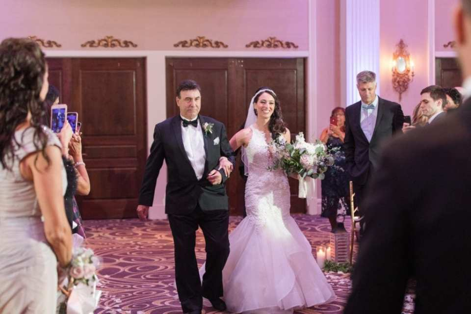 The bride being walked down the aisle by her father at the Palace at Somerset Park