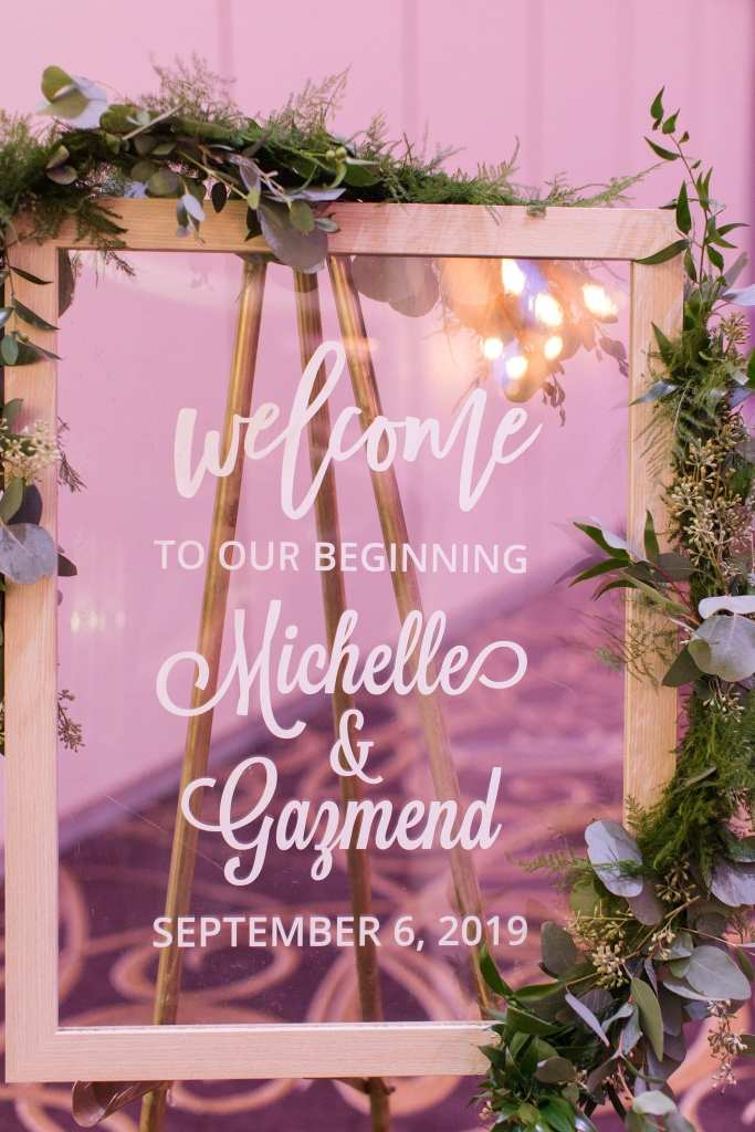 Acrylic welcome sign decorated with greens