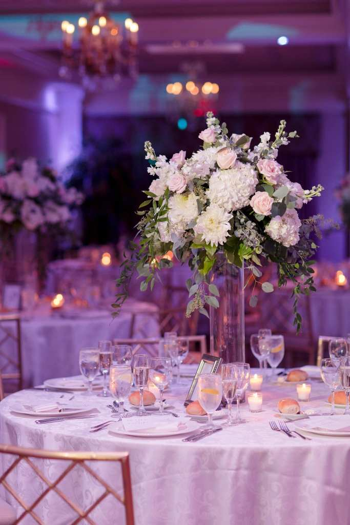 Tall floral arrangement of white and blush florals and greens on top of a clear cylinder vase by Jacquelines Florist at a Palace at Somerset Park wedding