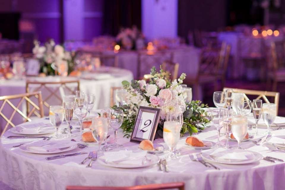 Reception table decorated with a low floral arrangement of light blush and white florals with greens by Jacquelines Florist at the Palace at Somerset Park
