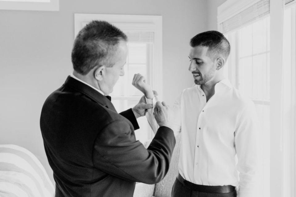 The grooms cufflinks being put in by his father