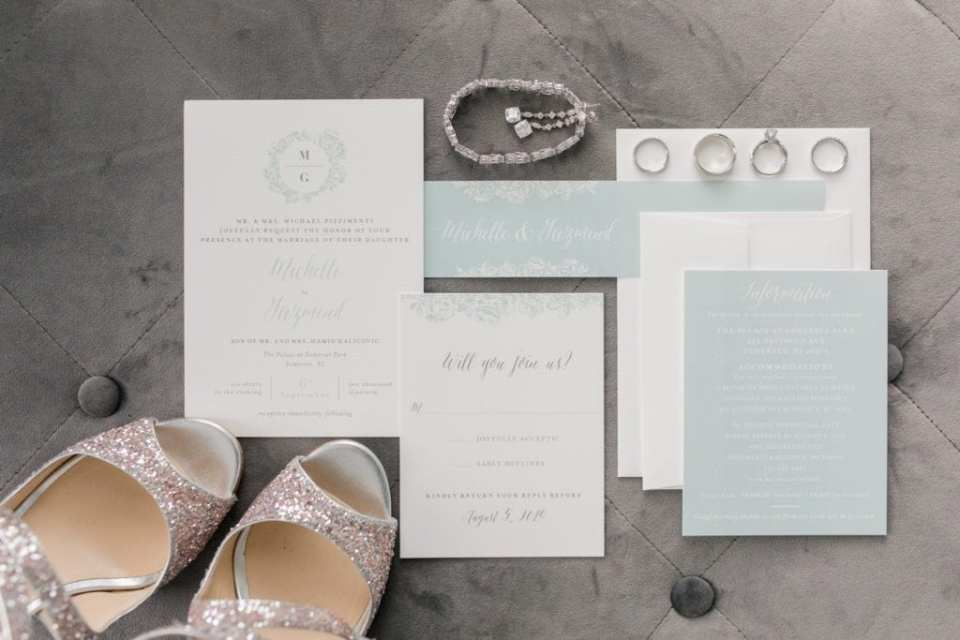 Wedding details: wedding invitation suite, brides Jimmy Choo sparkly heels, brides jewelry, wedding bands and engagement ring on gray background
