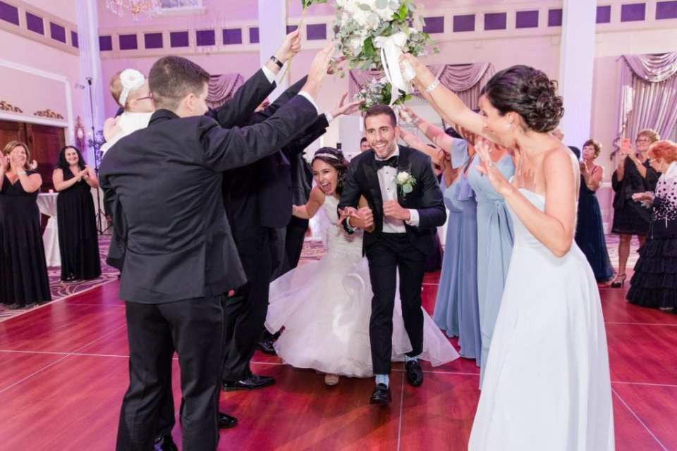 Bride and groom making their formal entry under a floral archway provided by their wedding party into the Palace at Somerset Park wedding