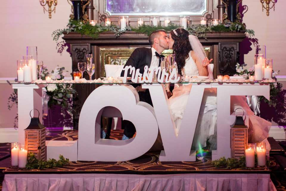 "Bride and groom kissing at their sweet heart table which is a wooden white table in the shape of the word LOVE the ""O"" in the shape of a heart, surrounded by candles at the Palace at Somerset Park"