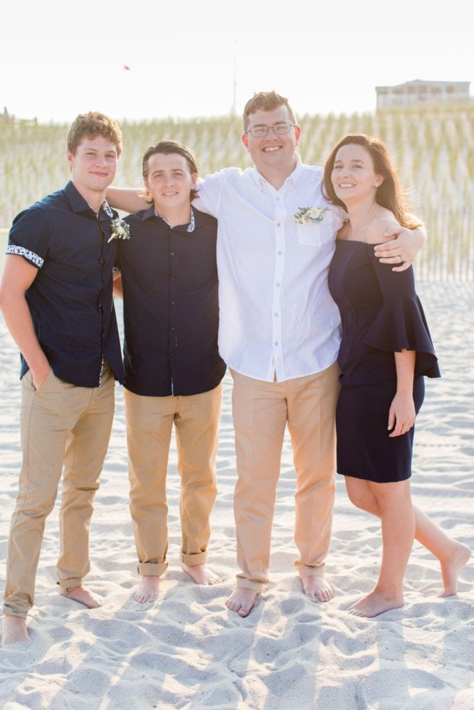 The groom in his casual white button down shirt and khakis, with family members dressed in black and khaki