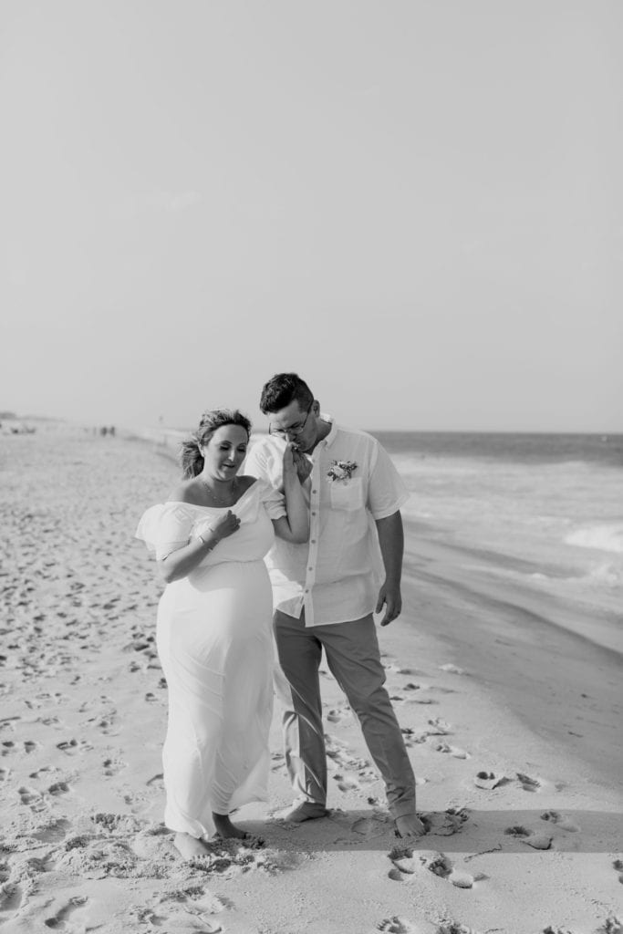 Black and white candid photo of the bride and groom on the beach; the groom is kissing his brides hand
