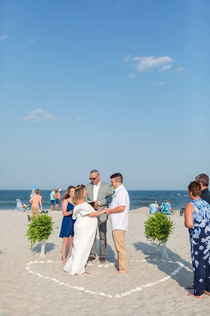 Bride and groom holding one anothers hands inside a heart shaped by shells during their Lavallette Beach elopement