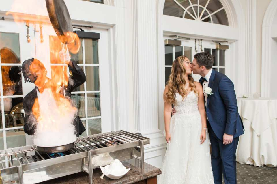Bride and groom kiss next to a chef flambe station at the Park Savoy Estate