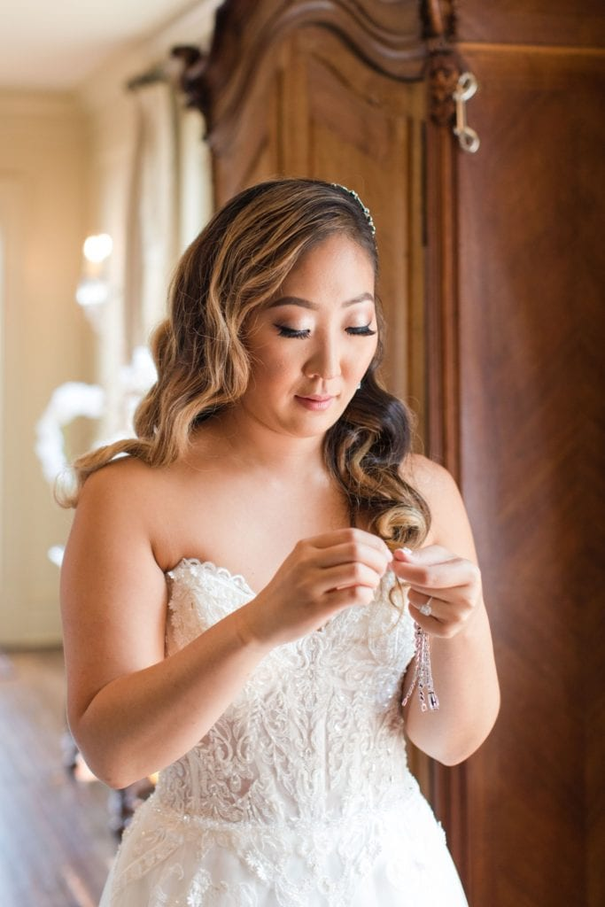 Bride putting the finishing touches on her gown, her necklace. Hair and makeup by The Glam Team
