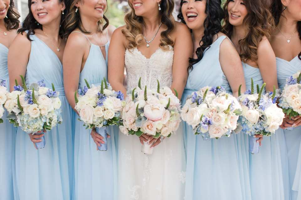 The bride and her bridesmaids in a casual fun picture, with their bouquets of off white florals with blue floral and greenery accents by Crest Florists highlighted