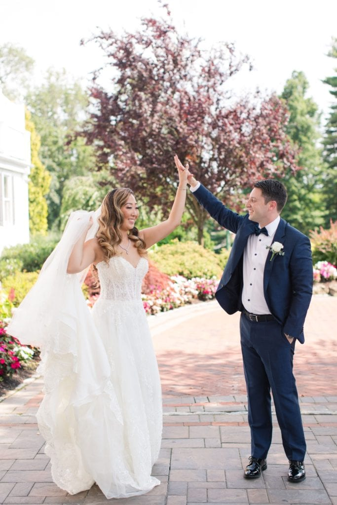The groom twirls his bride outside