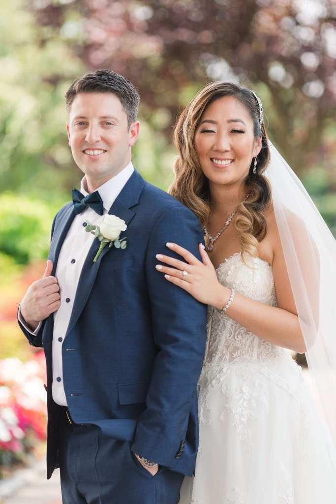 3/4 shot of the bride standing behind the groom, her left hand on his left forearm, both looking towards the camera and smiling
