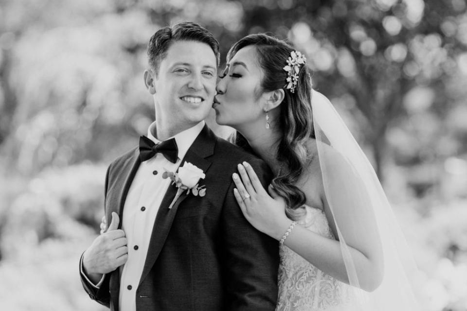 Black and white photo of the bride behind the groom, kissing his cheek as he smiles towards the camera