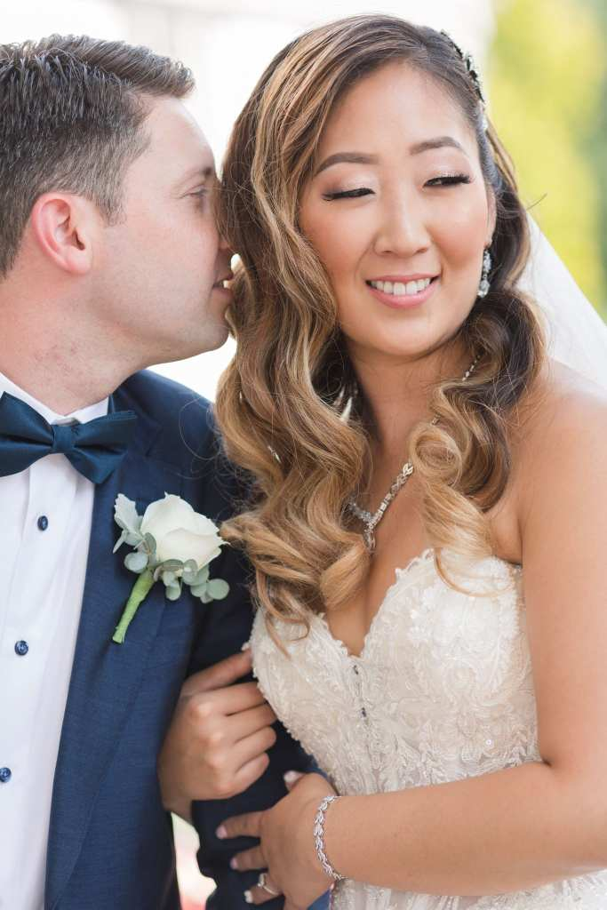 Close up of the bride smiling as her groom whispers into her ear
