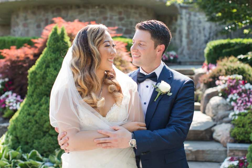 Bride wrapped up in grooms arms as they both look at each other, smiling
