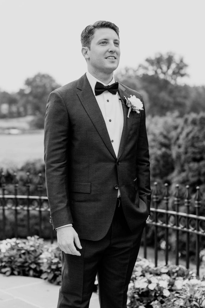 Black and white photo of the groom watching as his bride walks down the aisle