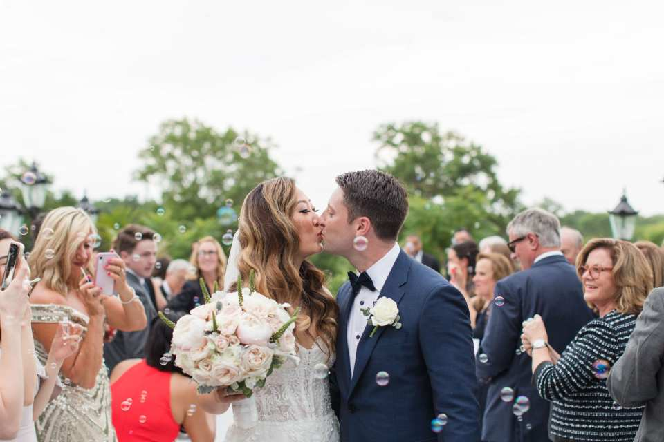 The newlyweds share a kiss at the end of the aisle as their guests look on and blow bubbles in their Park Savoy Estate wedding photos