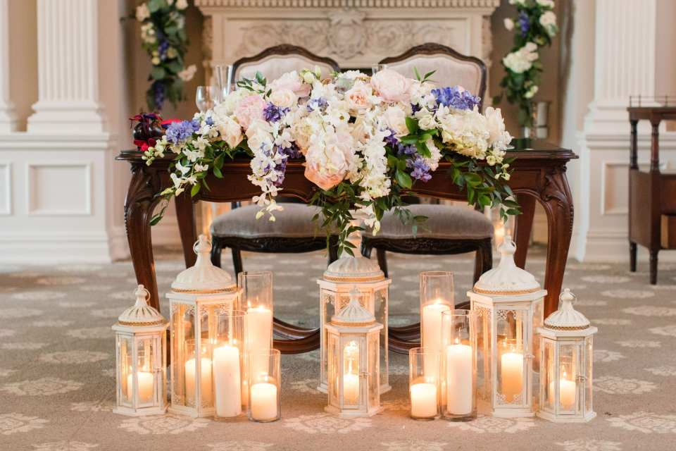 Close up of the sweetheart table decorated with a variety of pale colored flowers, with touches of purple scattered about. In front of the table is a set up of various candles and laterns in cream color