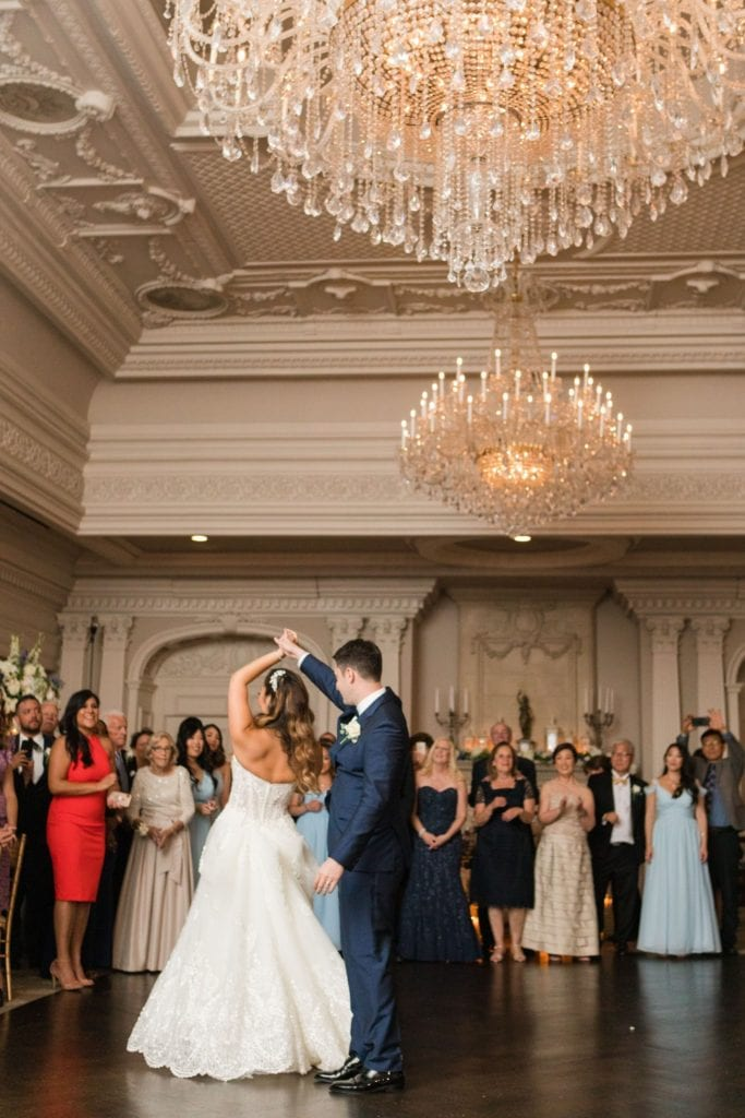 Full length vertical photo of the groom twirling his bride during their first dance; the guests stand behind them and watch