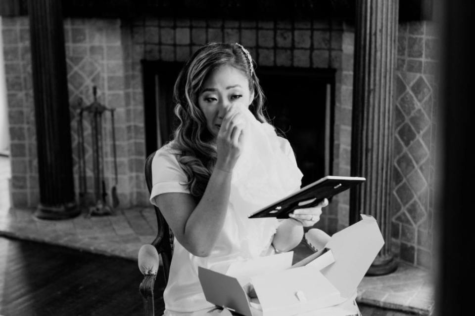 Black and white candid photo of the bride wiping away tears as she opens a gift from her groom