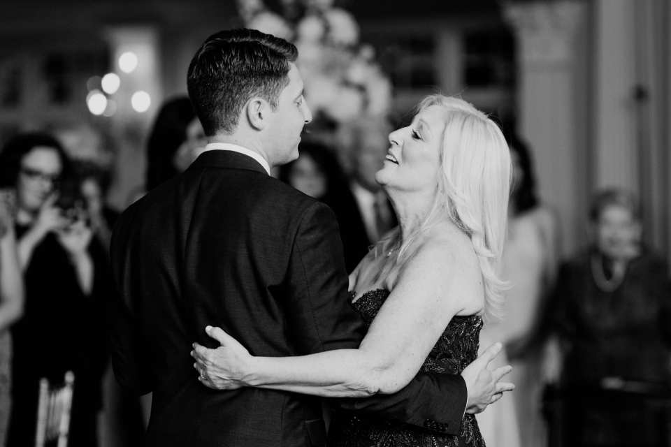 Black and white candid shot of the groom dancing with his mother