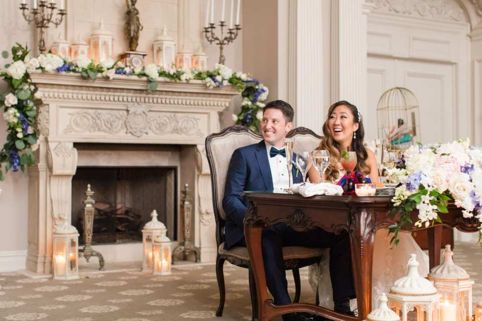 A candid of the bride and groom laughing, while sitting at the sweetheart table at the Park Savoy Estate
