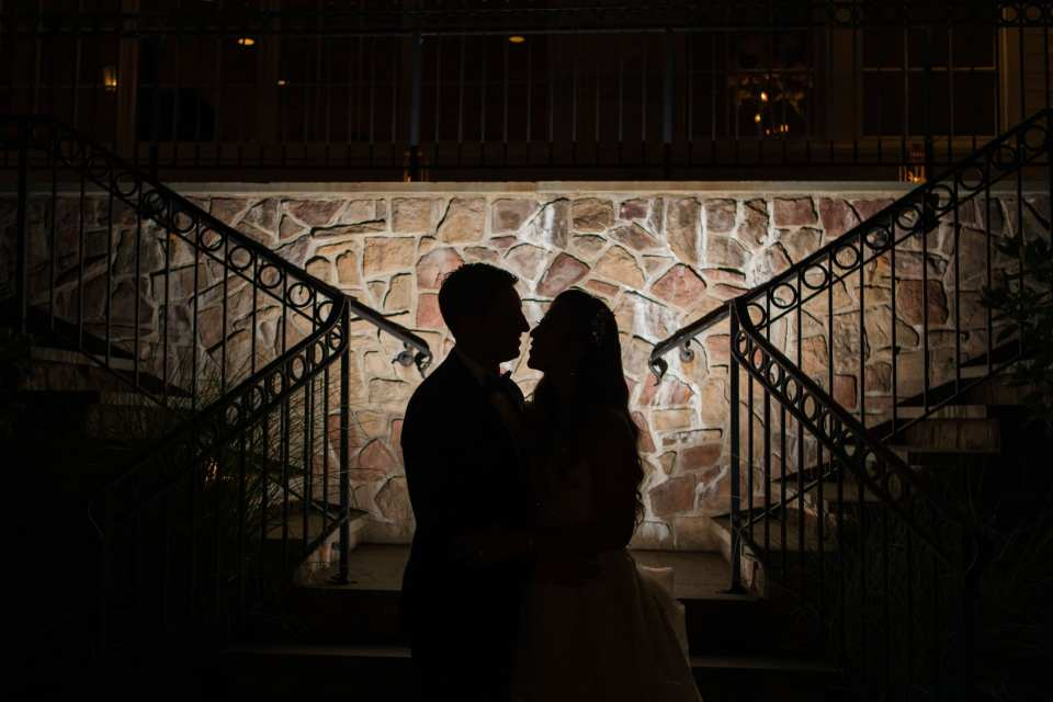Nighttime shadow portrait of the bride and groom facing each other outside the Park Savoy Estate