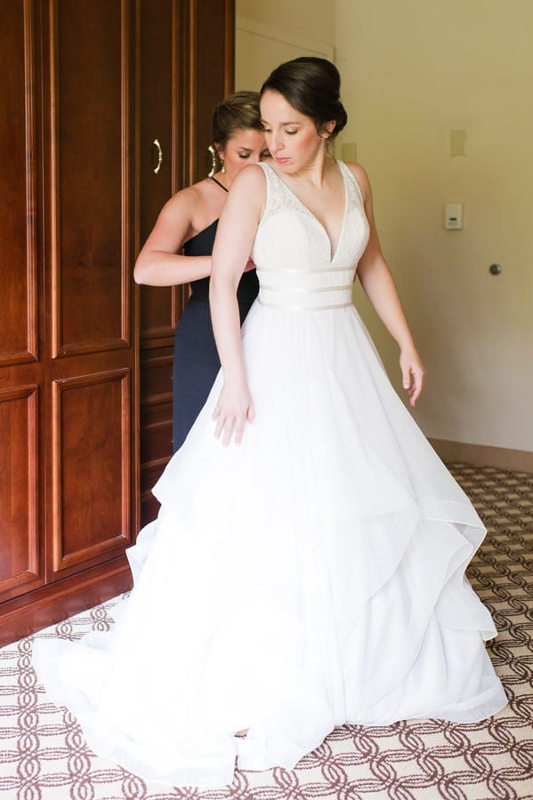 Full length photo of the bride being helped into her Mikaella Bridal gown by her maid of honor