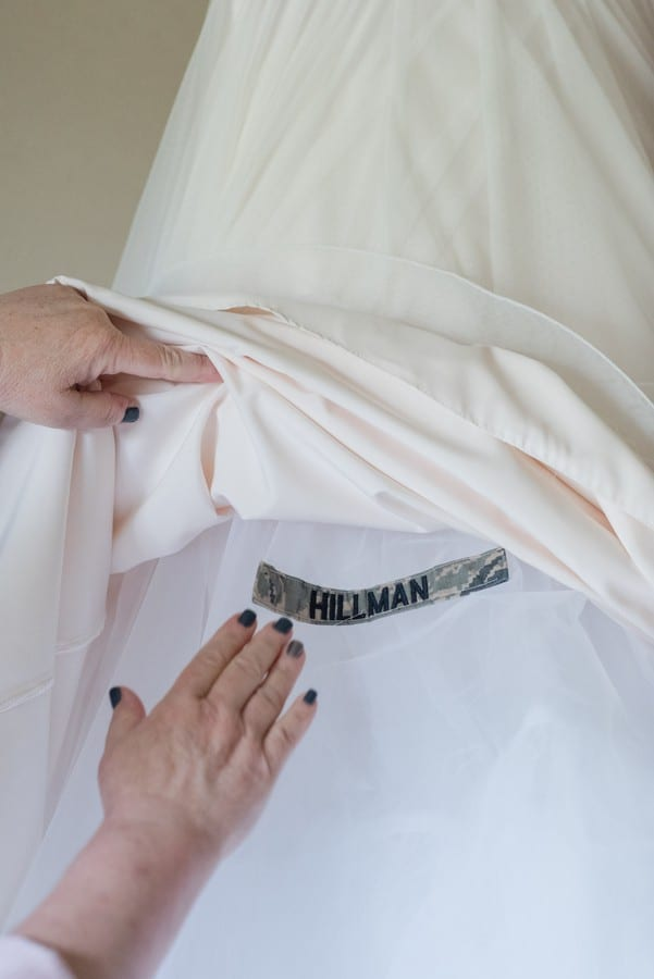 A tribute to the brides military family sewn into her wedding gown