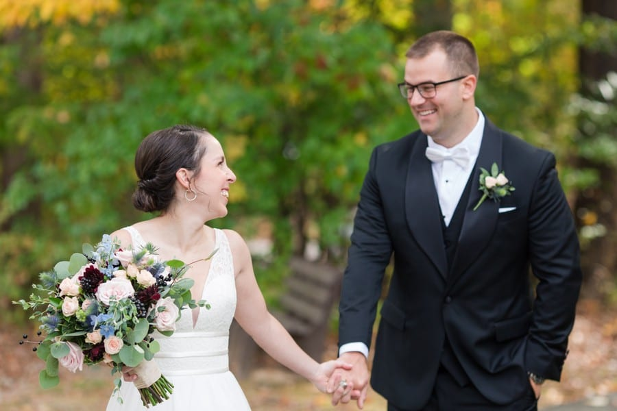 The bride and groom sharing a smile while holding hands during portraits