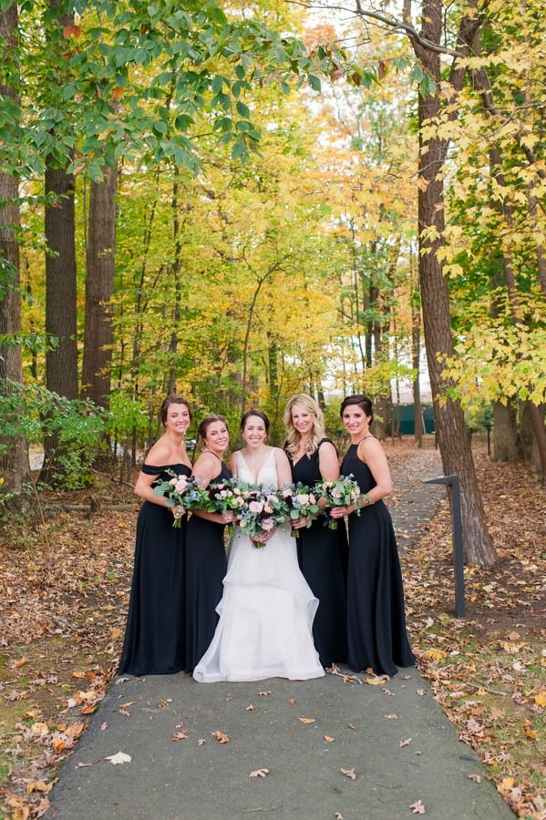 The bride in a gown by Mikella Bridal in a fun, full length photo with her bridal party in black gowns by Bill Levkoff, florals by Petal Pushers, outdoors at the Princeton Marriott at Forrestal