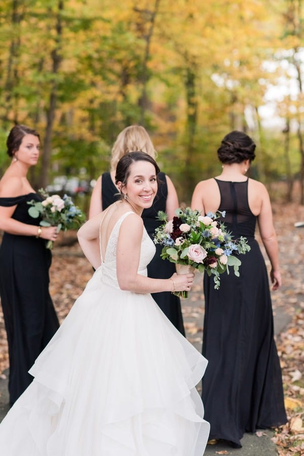 A fun portrait of the bride in Mikella Bridal looking back at the camera as she walks behinds her bridal party outdoors during portraits