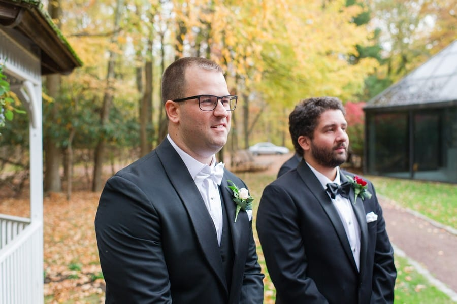The groom and his best man watch as the bride walks down the aisle