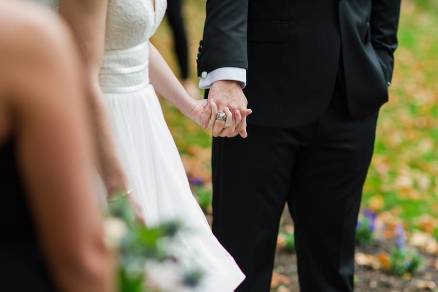 Close up of the bride and groom holding hands during the wedding vows