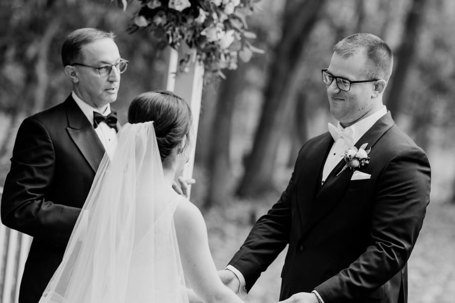 Black and white candid photo of the groom during the wedding vows