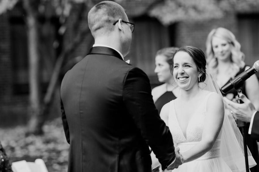 Black and white candid photo of the bride laughing during the wedding vows