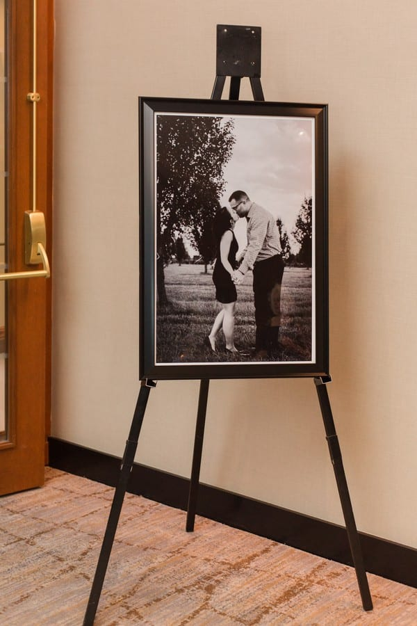 Black and white photo of the engaged couple at the entrance to their wedding reception