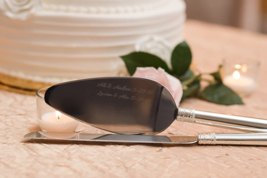 Wedding details: engraved family heirloom wedding cake knife and server with white patterned wedding cake by Cramers Bakery in the background