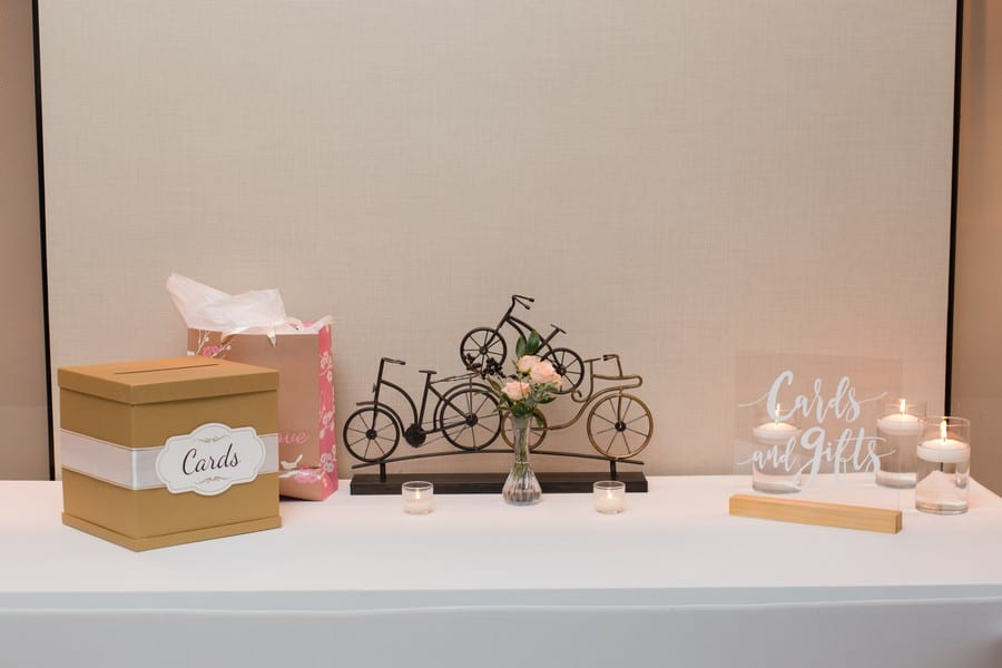 Wedding details: custom signage for cards and gifts set up against a wrought iron bicycle sculpture