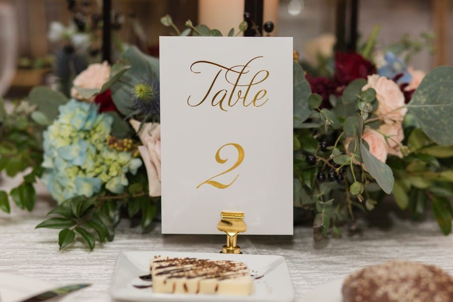 Wedding details: gold embossed table number with florals and greens behind it by Petal Pushers